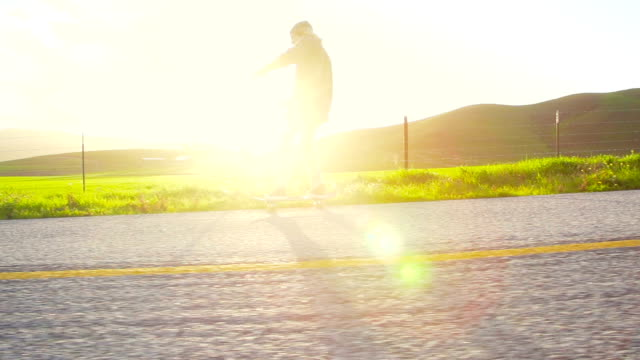 Slow Motion Skateboarder Riding Down Hill At Sunset video