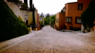 Slow motion steadicam of a cobble stone street with colorful houses and no cars video