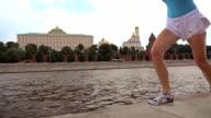 Slow motion steadicam shot of athletic brunette girl runner against Moscow Kremlin 240 fps video