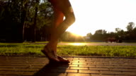 Slow motion steadicam shot of girl in sandals walking in summer sunset park video
