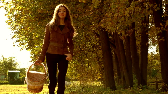 Slow motion steadicam video of a beautiful girl in brown jacket walking through autumn forest carrying a basket video