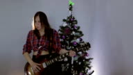 Slow motion. The teenage girl playing guitar, singing song and dancing near christmas tree. video