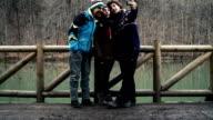 HD: Slow Motion Three Friend Taking Selfies near the Lake Outdoors video