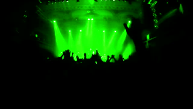 Slow motion video of cheering crowd during rock-concert. Green spotlights illuminating the venue. video
