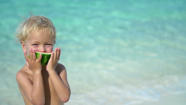slow motion video of child eating watermelon at a beach video