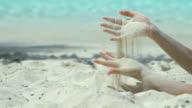 slow motion video of hands sifting the sand through fingers video