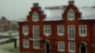 Slow motion video of snowflakes in front on red brick town house video