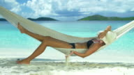 slow motion video of woman relaxing in beach hammock video