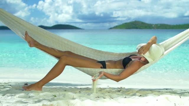 slow motion video of woman relaxing in beach hammock video