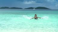 slow motion video of woman splashing in the ocean video