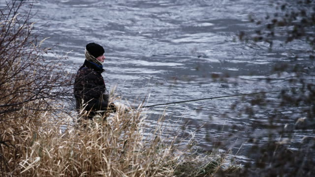 Slow motion view of a fly fisherman standing in the water behind some grass video