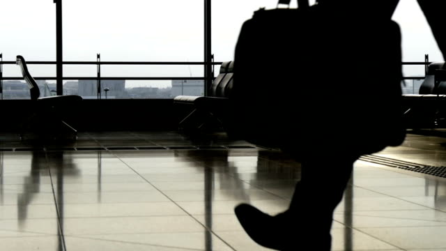 Slow motion view of anonymous commuters with luggage at the airport terminal. video