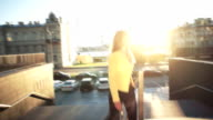 Slow motion. Young beautiful girl in a yellow jacket coming up the stairs. Business woman walking to work in the business center. Bright sunlight in the morning. Cinematic style video. Windly weather video
