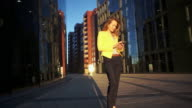 Slow motion. Young beautiful girl in a yellow jacket staying near office with the phone. Business woman using smartphone at the business center. Bright sunlight in the morning. Cinematic style video video