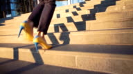 Slow motion. Young beautiful girl in a yellow shoes on hi heels coming up the stairs. Cinematic style video. View on legs and yellow-blue shoes video