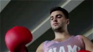 Slow motion. Young boxer takes off red gloves after a workout. video