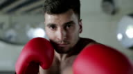 Slow motion. Young boxer with a confident eyes is waiting the fight. video