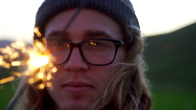 Slow Motion Young Man Staring At Sparkler At Sunset video