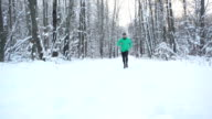 Slow Motion Young Sportsman Running Through Snowy Forest. Training and exercising outdoors when cross country running in inspirational winter landscape. Sports Motivation. video