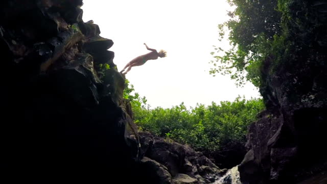 Slow Motion Young Woman Back Flip Jumps off Cliff Into Water. Lush Green Jungle Waterfall Pond. video