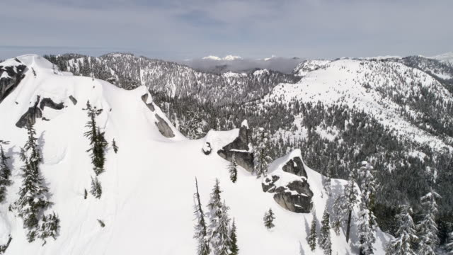 Slow Rotating Aerial of Cascade Mountain Range Summit with Cliffs of Powder Snow in Washington State video