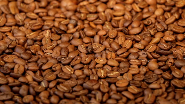 Slow rotation of the heap of coffee beans. Close up of coffee beans. Loopable rotation video