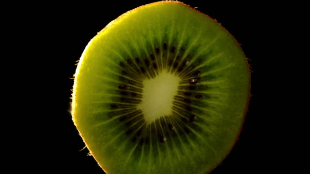Slow zoom in on Kiwi tropical fruit with black background video