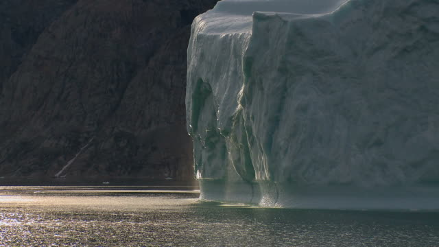 Slowly sailing pass a huge iceberg with water running Greenland video
