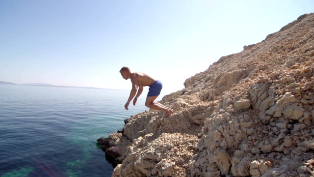 Slow-Mo: Fit Guy Jumping Head First Into Clear Blue Water video