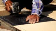 slow-motion, construction worker using hammer tiling floor video