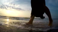 Slow-motion footage of a woman's feet stepping on the sand beach at sunset video