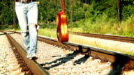 Slow-motion footage of a young guitarist in ripped jeans walking along the rail video