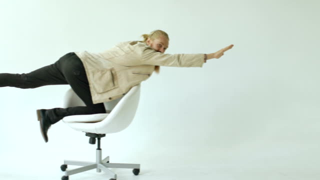 Slowmotion of Bearded funny businessman have fun riding on office chair on white background video
