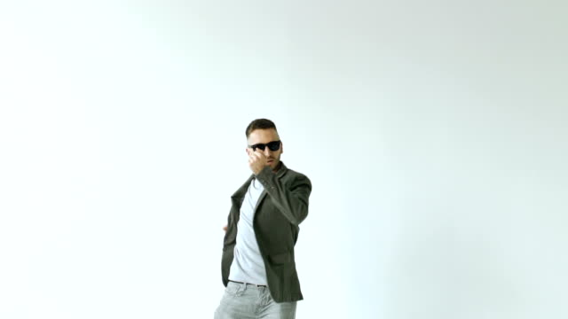 Slowmotion of Young funny man in sunglasses crazy dancing on white background video