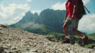 Slow-motion senior man trail hiking on high mountain video