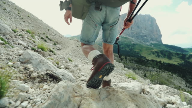 Slow-motion senior man trail hiking on mountain video