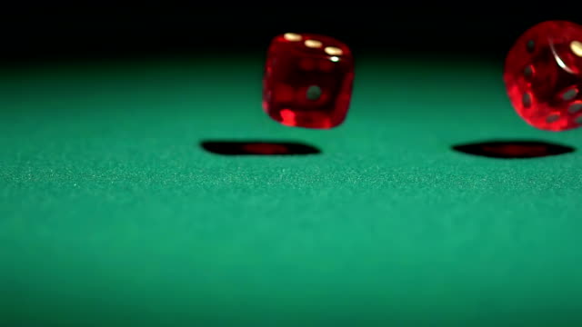 Slow-motion video of gambling game, red dice falling on green video