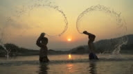 HD Slowmotion:Silhouette happy child splashing played in pond at sunset. video