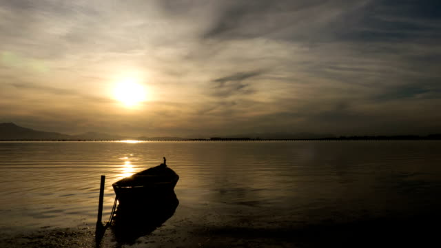 Small boat on lake at sunset. video