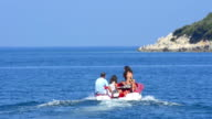 Small boat with people go to rocky island video