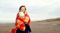 MS Small boy and girl wrapped in blanket on beach video