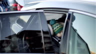 A small boy in a child seat in the back seat of the car. video