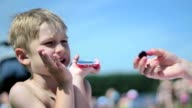Small boy on the beach does not want to eat. Boy is not hungry video