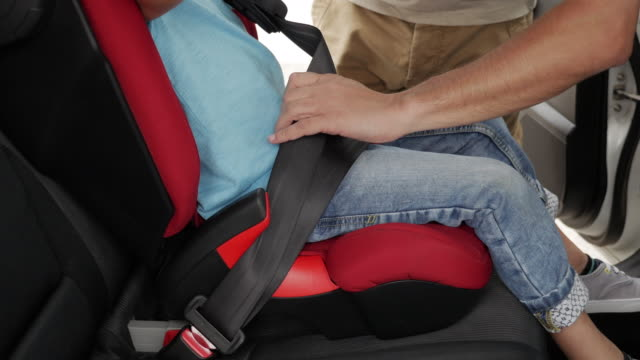 Small boy smiling while his father helps to fasten belt on car seat video