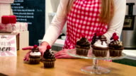 Small business owner in cake shop serving cupcakes video