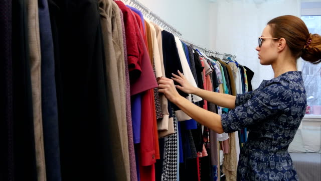 Small business owner in clothes shop checking collection video
