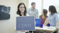 Small business startup company holding a 'We are Open' sign video