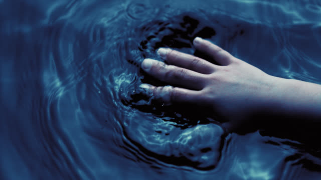 SLO MO of small children's hand touching the surface of water video