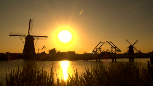 Small drawbridge on river with traditional windmills in background at sunset video