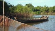 Small dugout canoe tied up to bamboo pole and fishing net spread across river video